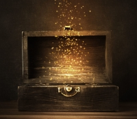[Art by: Alexis Goble] Glowing golden sparkles and stars rising from an old, opened wooden treasure chest. Darkly lit on a planked surface with black chalkboard background.